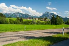 Straße vor den Alpen Stockfotos
