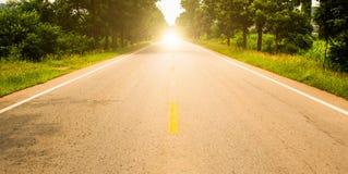 Straße voran und der Sonnenaufgang Stockfotografie