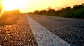 Straße voran und der Sonnenuntergang Stockfotografie