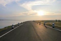 Straße an Wasserreservoir Phra Satung gegen Himmel während des Sonnenuntergangs Lizenzfreies Stockbild