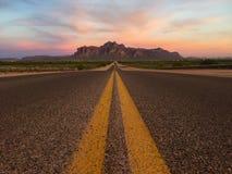 Straße zu den Bergen bei Sonnenuntergang Lizenzfreie Stockbilder
