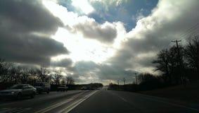 Straße zu den Winter-Wolken im blauen Himmel Stockfoto