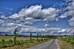 Straße zu einer Ferne zwischen Feldern Stockbilder