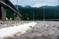 Straße zum Berg und zum elektrischen Pfosten Lizenzfreies Stockfoto