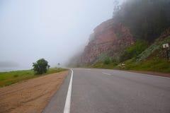 Straße zum Horizont im Nebel Einsame Weise in Sibirien Sommer Stockbild