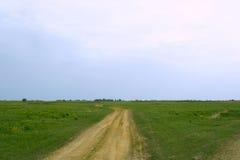 Straße zum Horizont und zum tiefen blauen Himmel Lizenzfreies Stockfoto