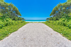Straße zum Paradies, aphalt Stangenende auf tropischem Strand mit TürkisMeerwasser Stockbild
