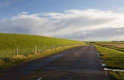 Straße zwischen grünen Hügeln und blauem Himmel lizenzfreie stockfotografie