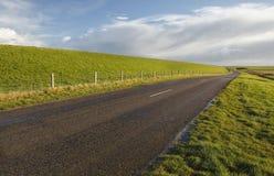 Straße zwischen Hügeln des grünen Grases unter blauem Himmel stockfoto