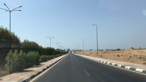 Straße zwischen Palmen durch die Wüste stock footage