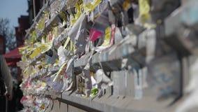 Straßen-Anzeigen-Papier geschrieben auf dem Zaun in der Stadt stock footage