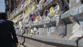 Straßen-Anzeigen-Papier geschrieben auf dem Zaun in der Stadt stock video