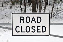 Straßen-geschlossenes Zeichen mit Snowy Forst im Hintergrund Stockfoto