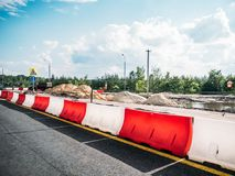 Straßen-Reparatur-, Sandstapel und fechten Sperren und Verkehrs-kegel, Landstraßenasphaltverbesserung Stockbild