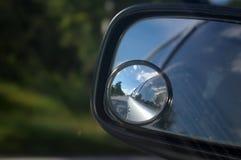 Straßenansicht in eine Autospiegelreflexion lizenzfreies stockfoto
