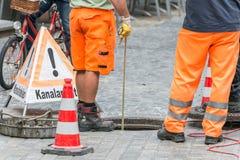 Straßenarbeiten über Abwasserkanalkanal mit warnen unterzeichnen herein deutsche Wörter für Kanalarbeiten Lizenzfreie Stockfotos