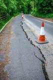Straßenarbeiten auf gebrochenem Asphalt von der Senkung Lizenzfreie Stockbilder