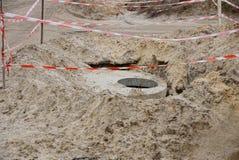 Straßenarbeiten mit einem Stapel des Landes und der konkreten Entwässerung brüten aus Lizenzfreies Stockbild