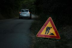 ` Straßenarbeiten voran ` Zeichen auf der Seite einer Straße Stockbild