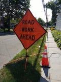 Straßenarbeiten-voran Zeichen mit orange reflektierendem Verkehrssicherheits-Kegel Lizenzfreies Stockfoto
