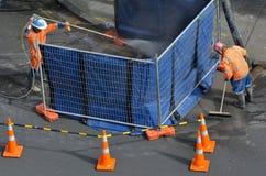 Straßenarbeiter, der Abwasser in der Stadtstraße säubert Lizenzfreie Stockfotos
