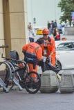 Straßenarbeiter säubert die Behälter des Rückstands stockfotos