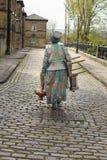 Straßenausführender macht ihren Heimweg über den Kopfsteinen stockbild