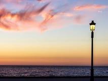 Straßenbeleuchtung, die den Sonnenuntergang aufpasst Lizenzfreie Stockfotografie