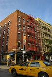 Straßenbild in der Nolita-Nachbarschaft, wenn ein Taxi vor dem Gebäude überschreitet, in der Stadt New York Stockfotos