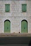 Straßenbild - Steinwand mit grünen Türen und Fenstern Stockbilder