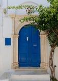 Straßenbild und blauer hölzerner Eingang auf ägäischen Inseln von Tinos, Griechenland stockfotografie
