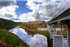Straßenbrücke über dem Fluss mit Unterstützungen auf dem Hintergrund des Herbstwaldes und buntem Himmel mit Wolken stockfotos
