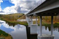 Straßenbrücke über dem Fluss mit Unterstützungen auf dem Hintergrund des Herbstwaldes und buntem Himmel mit Wolken lizenzfreie stockbilder