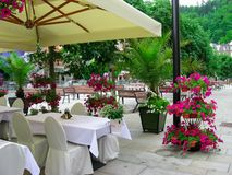 Straßencafé unter Überdachung, leere Tabellen mit weißen tableclothes zur Abendessenzeit Grüne gemütliche Straße lizenzfreie stockfotos