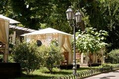 Straßencaféinnenraum im grünen Stadtpark, der mit Blumen, Sommersaison, heller sonniger Tag aufwändig ist, brüniert getont Stockfotografie