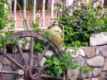 Straßendekoration des Cafés: Blumen, ein altes Wagenrad und alter Lehmkrug stockbilder