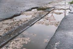 Straßenentwässerung auf dem Straßenrand, Reflexion der Umwelt im Wasser Lizenzfreie Stockbilder