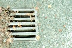 Straßenentwässerungs-Abwasserkanalsystem mit Metallgitterabdeckung Stockfotos