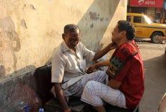 Straßenfriseur, der einen Mann verwendet eine offene Rasierklinge auf einer Straße in Kolkata rasiert Lizenzfreie Stockfotografie