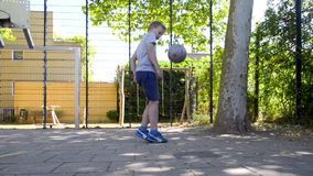 Straßenfußballjunge, der Keepie Uppie spielt stock video footage