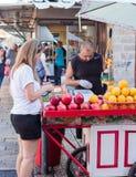 Straßenhändler bereitet frischen Saft zu den Frauenkunden zu Stockfoto