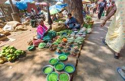 Straßenhändler, die grüne Erbsen und anderes Gemüse vom Boden verkaufen Lizenzfreies Stockfoto
