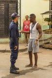 Straßenhändlermann, der mit Polizeibeamten Havana spricht Lizenzfreie Stockfotografie