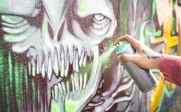 Straßenkünstler, der bunte Monstergraffiti auf allgemeiner Wand malt Stockfoto