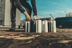 Straßenkünstler, der Dosen mit bunter Sprühfarbe nimmt Stockfotografie