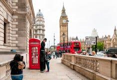 Straßenkünstler führen vor einer roten Telefonzelle durch Stockfoto