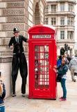 Straßenkünstler führen vor einer roten Telefonzelle durch Stockbild