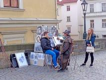 Straßenkünstler malt ein Porträt Stockbilder