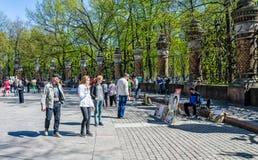 Straßenkünstler und theyr Zuschauer nahe dem Zaun von Mikhailovsky arbeiten im Garten Stockbild