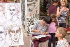 Straßenkarikaturist zeichnet eine Karikatur Lizenzfreie Stockfotografie